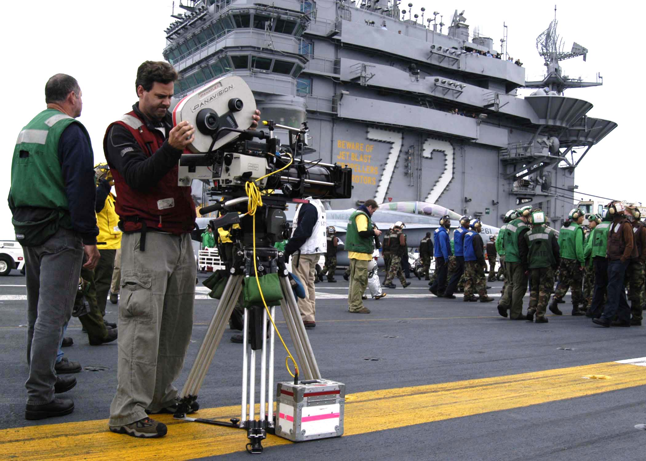 "Aboard USS Abraham Lincoln (CVN 72) June 15, 2004--With crew of USS Abrahm Lincoln in front of the camera, the crew of the upcoming movie ""Stealth"" set up for scenes to be taped on the flight deck.  After 10 1/2 months of Dry Docked Planned Incremental Availability (DPIA), Abraham Lincoln is currently conducting local operations in preparation for deployment next year.  U.S. Navy photo by PH3(AW) Tyler J. Clements.  Approved for release by ALSG Public Affairs Officer LCDR John Daniels."